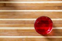 Boisson rouge sur le plancher en bambou Images stock