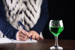 Boisson verte d'absinthe dans le carnet d'histoire d'écriture en verre et de femme photos libres de droits