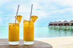 Boissons avec une paille sur une table en bois sur le fond d'une plage sablonneuse et des maisons sur l'eau photos libres de droits