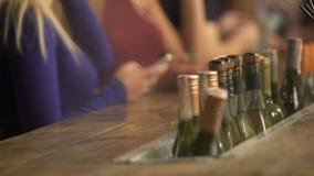 Boissons de commande décontractées des jeunes à la barre, vérifiant des messages sur des smartphones clips vidéos