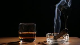 Boissons de whiskey avec les cigares de tabagisme banque de vidéos