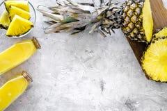 Boissons non alcoolisées Bouteille avec le jus de fruit près des tranches d'ananas sur le copyspace gris de vue supérieure de fon Photographie stock
