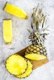Boissons non alcoolisées Bouteille avec le jus de fruit près des tranches d'ananas sur la vue supérieure de fond gris Photographie stock libre de droits