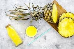 Boissons non alcoolisées Bouteille avec le jus de fruit près des tranches d'ananas sur la vue supérieure de fond gris Photos libres de droits