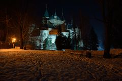 Bojnice castle in winter night. One of the most beautiful castles in Slovakia - Bojnice. In front park covered with snow, lighted by incadescent lights, in Royalty Free Stock Images