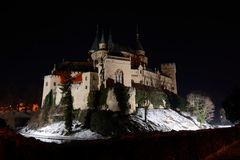 Bojnice castle in winter night. One of the most beautiful castles in Slovakia - Bojnice. In front stone wall lighted by incadescent lights, in background dark Royalty Free Stock Photo
