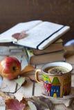 Bok, anteckningsbok och kopp av varmt te Arkivbilder