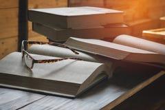 bok, blyertspenna och exponeringsglas Arkivfoton