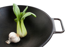 Bok Choy and Garlic in a Wok. A single stalk of baby bok choy and a garlic bulb in a black wok Stock Image