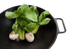 Bok Choy Stalks and Garlic in a Wok. Stalks of baby bok choy and two garlic bulbs in a black wok Royalty Free Stock Images