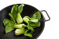 Bok Choy in a Wok. Four Stalks of baby bok choy in a black wok Royalty Free Stock Photos