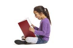 Bok för avläsning för skolaflicka sittande Royaltyfri Bild
