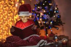 Bok för jul för förvånad barnöppning magisk royaltyfri bild