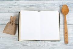 Bok för receptkockmellanrum på träbakgrund, sked, kavel, rutig bordduk Arkivfoto