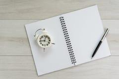 Bok för tom sida för öppning vit pappers- med pennan och ringklockan på royaltyfri fotografi