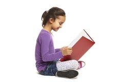 Bok för avläsning för skolaflicka sittande Arkivfoto