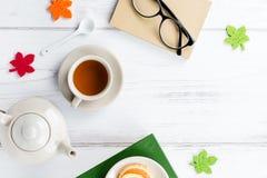 Bok, kopp te, tekanna, sötsaker och glasögon, lekmanna- lägenhet Hemtrevlig bakgrund, läs- begrepp kopiera avstånd royaltyfria bilder