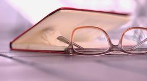 Bok med ögonexponeringsglas royaltyfri bild