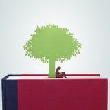 Bok med flickaläsning under trädpapperssnittet Arkivfoto