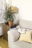 Bok och exponeringsglas på överkanten av armen av en soffa royaltyfri bild