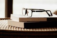Bok och exponeringsglas överst av rottingmöblemang, i modern husintelligens Royaltyfri Fotografi