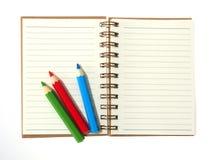 Bok och färgrika blyertspennor som isoleras på vit bakgrund Royaltyfri Bild