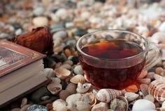 Bok och genomskinlig glass kopp med teanseende Royaltyfri Foto