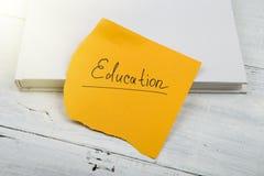 Bok och gult ark med & x22; education& x22; inskrift på en vit wo royaltyfri bild