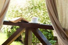Bok och kaffe i den trädgårds- terrassen royaltyfria foton