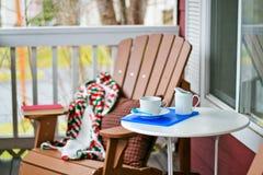 Bok och kaffe på en hemtrevlig farstubro fotografering för bildbyråer