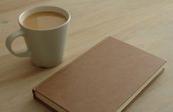 Bok och kaffe på en tabell Arkivfoton