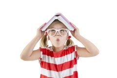 Bok och le för flickaskolflickainnehav Royaltyfria Foton