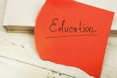 Bok och rött ark med & x22; education& x22; inskrift på en vit woode arkivbilder