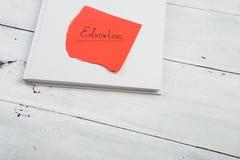 Bok och rött ark med & x22; education& x22; inskrift på en vit woode royaltyfri fotografi