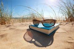 Bok och solglasögon på stranden Fotografering för Bildbyråer