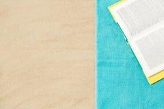 Bok på strandhandduken på sand arkivfoton