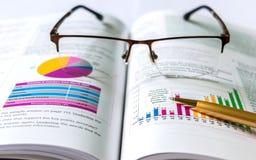 Bok, penna, glasögon och diagram arkivbild