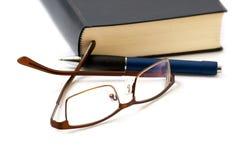 Bok, penna och exponeringsglas Royaltyfria Foton