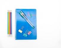 Bok, pennor, blyertspennor och gem Arkivfoto
