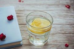 boka exponeringsglas- och blommakronbladexponeringsglas av vatten med citronen Arkivbild