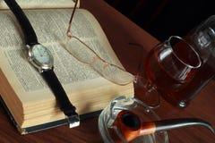 Boka, exponeringsglas och cognacen Royaltyfria Bilder