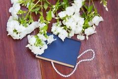 Boka med vita blommor och pryda med pärlor halsbandet på träbakgrund Fotografering för Bildbyråer