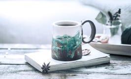 Boka och en kopp te på en träbakgrund Fotografering för Bildbyråer