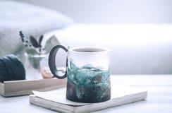 Boka och en kopp te på en träbakgrund Royaltyfria Foton