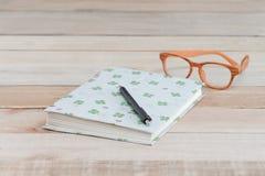 Boka och pennan, monokel på den wood tabellen arkivfoto