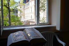 Boka på tabellen framme av fönstret arkivfoto