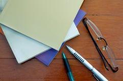 Boka pennan och exponeringsglas på den röda wood tabellen Arkivbild