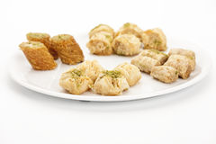 Bokaj Cashew Baklava Amidst Oriental Pastries. Four pieces of Bokaj cashew baklava presented with assorted oriental sweet pastries on a white plate. Flower Stock Photos