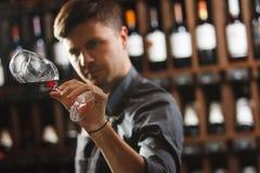 Bokal czerwone wino na tle, męski sommelier docenia napój fotografia royalty free