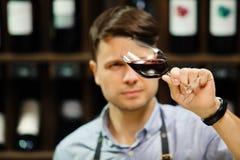 Bokal czerwone wino na tle, męski sommelier docenia napój zdjęcia royalty free